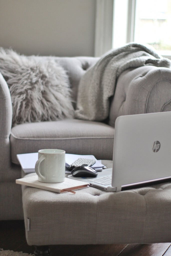 Grey sofa and soft furnishings with laptop looking at growing email list with Pinterest