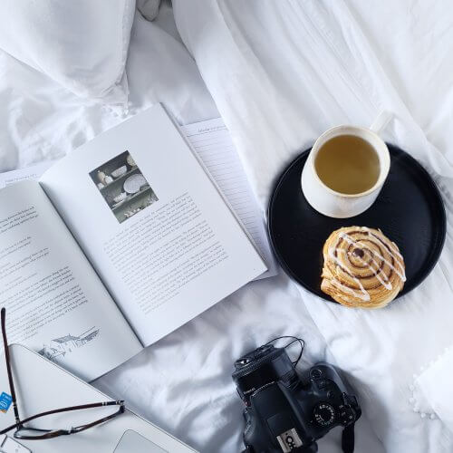 Flatlay of a book, cup of green tea and a cinnamon swirl. Photo by Wildflower, Pinterest Management Service