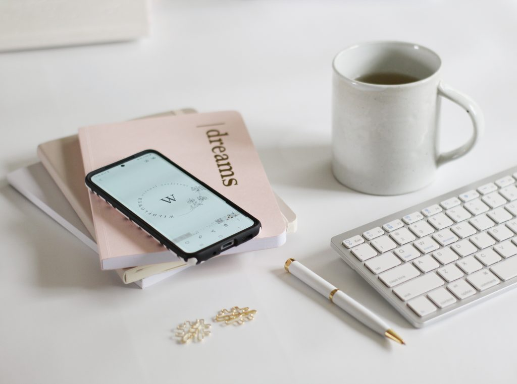 "Desk top flat lay image of notebooks, cup of tea and phone used for the web post ""how to claim a website in Pinterest"" by Wildflower Pinterest Management"