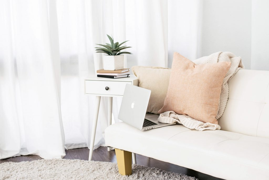 Stock photograph of a laptop on a white sofa