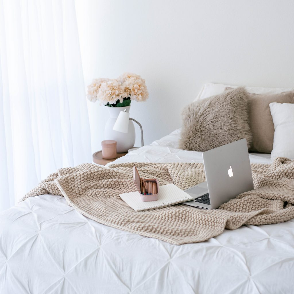 Image of grey cushions and beige blanket on bed with laptop from an article on marketing for introverts on Pinterest by Wildflower Pinterest Manager