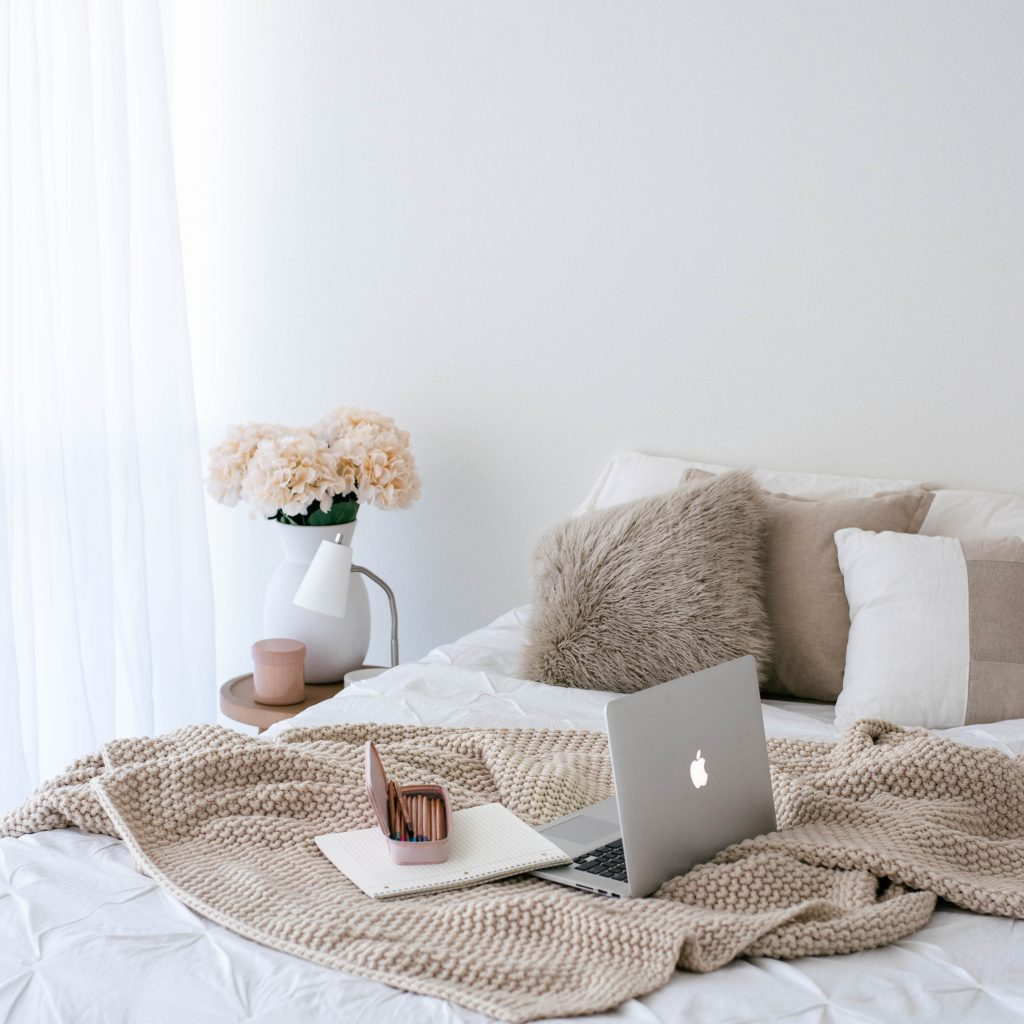 Cosy neutral bedroom with laptop on the bed -