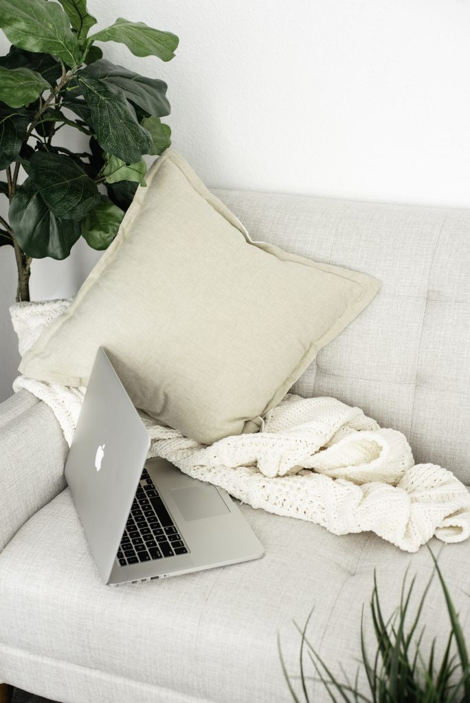 Image of grey cushions and beige blanket on sofa with laptop from an article on marketing for introverts on Pinterest by Wildflower Pinterest Manager