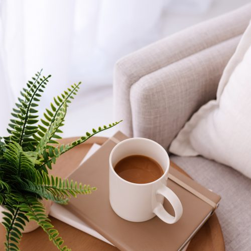 Desk top scene with fern, coffee cup and notebook - Wildflower Pinterest Management